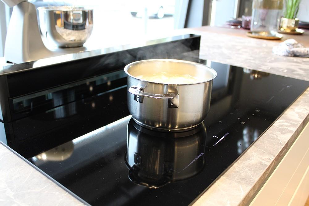 Das ist praktisch: Der Lüftungsschirm der Abzugshaube lässt sich einfach per Knopfdruck bedienen. Er verschwindet nach Gebrauch wieder unsichtbar im Kochfeld. Dabei lässt er sich auf verschiedene Höhen einstellen, um so effektiv und direkt am Kochgeschirr abzusaugen.  Foto: Studio187